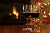 Red wine next to the Christmas tree in front of the fireplace.